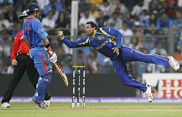 Tillakaratne Dilshan (right) dives full stretch to take a successful return catch to dismiss Kohli