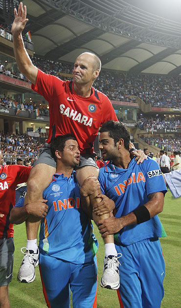 Gary Kirsten is lifted by Suresh Raina (left) and Virat Kohli (right)