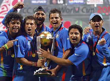Tendulkar and members of the Indian team celebrate with the trophy.
