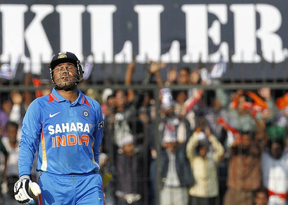 Virender Sehwag celebrates scoring a century during the fourth One-day against the West Indies in Indore