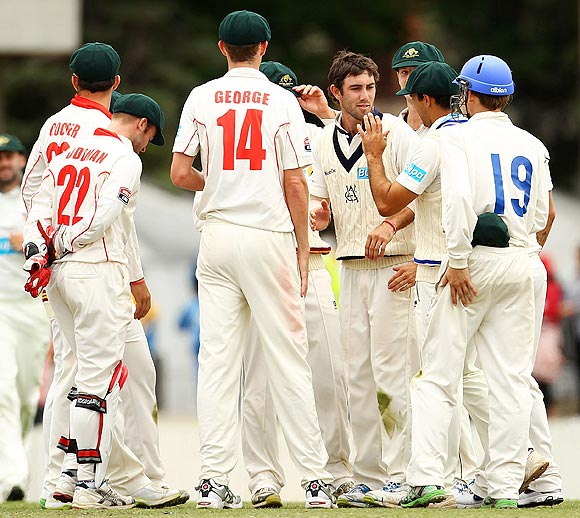 Cameron Boyce of the Chairman's XI is congratulated by teammates after dismissing Virat Kohli