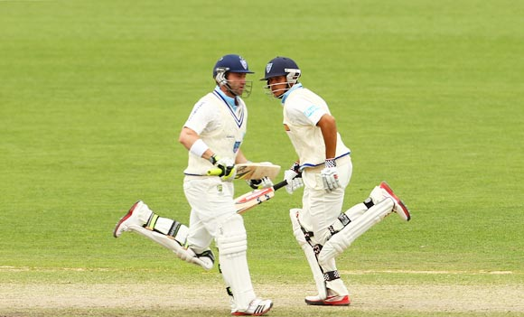 Phillip Hughes (left) and Usman Khawaja run between the wickets