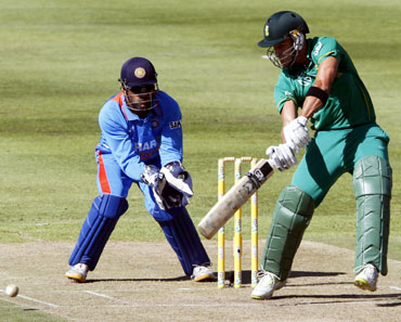 South Africa's Faf du Plessis (R) plays a shot as India's keeper MS Dhoni looks on during their third one-day international cricket match in Cape Town
