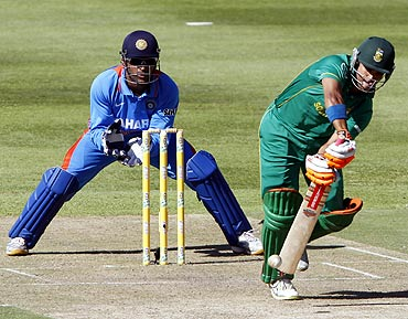 South Africa's JP Duminy (R) plays a shot as India's keeper MS Dhoni looks on during their third one-day international cricket match in Cape Town