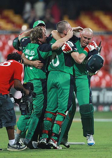 Trent Johnston of Ireland is mobbed by teammates after Ireland beat England