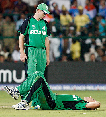 Trent Johnston of Ireland goes down after injuring his knee while bowling