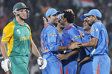 Graeme Smith (left) walks off the field after he was dismissed by Zaheer Khan (centre)