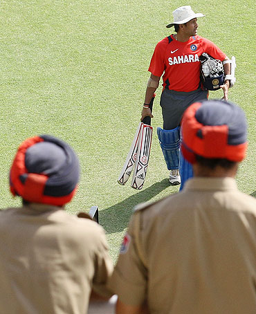 Sachin Tendulkar walks across the field while being watched by two policemen