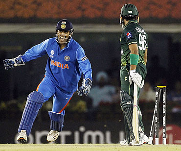 India's captain and wicketkeeper Mahendra Singh Dhoni (left) celebrates after Pakistan's Umar Akmal (right) is bowled by Harbhajan Singh