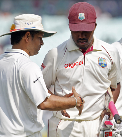 Sachin Tendulkar (L) congratulates Bravo on his century