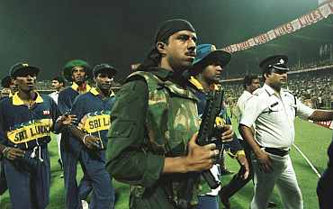 Riot police lead the Sri Lankan team off the pitch after the abandonment of the semi-final in the Cricket World Cup between India and Sri Lanka