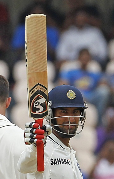 India's Cheteshwar Pujara raises his bat to celebrate scoring a half century during the first day of their first Test match
