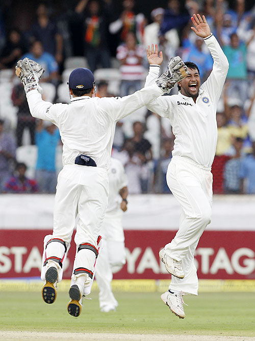 Pragyan Ojha (right) celebrates with captain Mahendra Singh Dhoni after claiming the wicket of Brendon McCullum