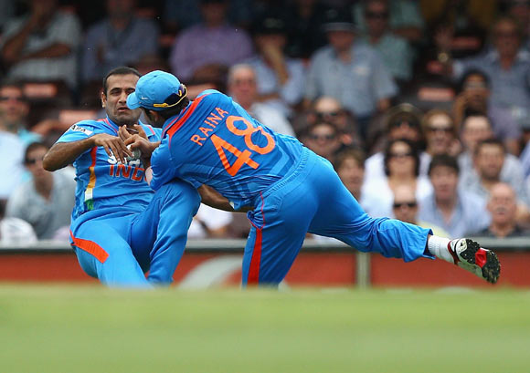 Suresh Raina of India collides with Irfan Pathan of India after Raina took a catch to dismiss David Warner of Australia