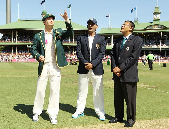 Australia captain Michael Clarke tosses the coin as Mahendra Singh Dhoni looks on