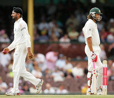 Harbhajan Singh of India walks past Andrew Symonds