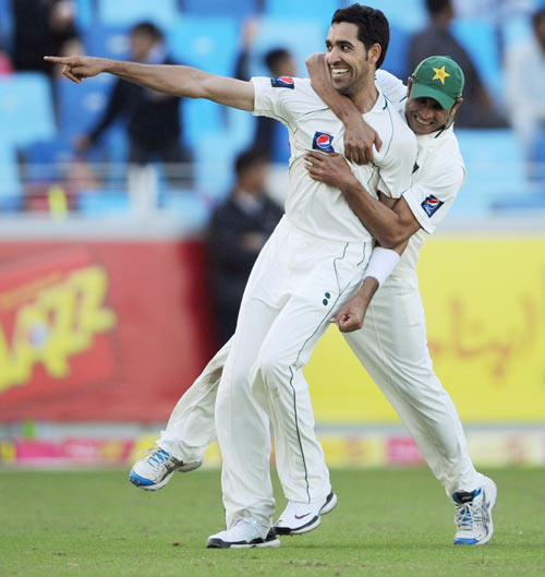 Umar Gul of Pakistan celebrates with Abdur Rehman after dismissing Jonathan Trott of England during the first Test match