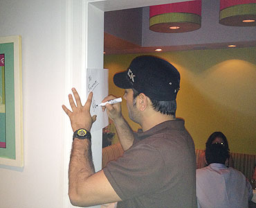 Dhoni signs an autograph for a fan