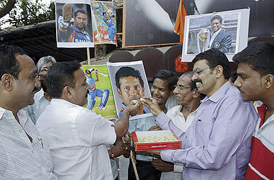 Fans Sachin Tendulkar celebrate his 100th international century on the outskirts of Mumbai on Friday