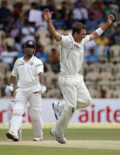 New Zealand's Tim Southee celebrates taking the wicket of India's MS Dhoni during their second Test match in Bangalore