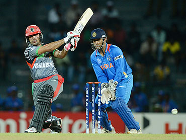 Afghanistan's Mohammad Nabi plays a shot on the on side as MS Dhoni watches