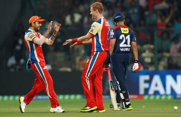 Andrew McDonald and Virat Kohli celebrate the wicket of Virender Sehwag on Tuesday