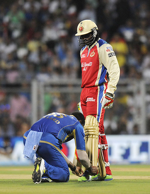 Kieron Pollard of Mumbai Indians helps Chris Gayle of Royal Challengers Bangalore tie his shoe laces