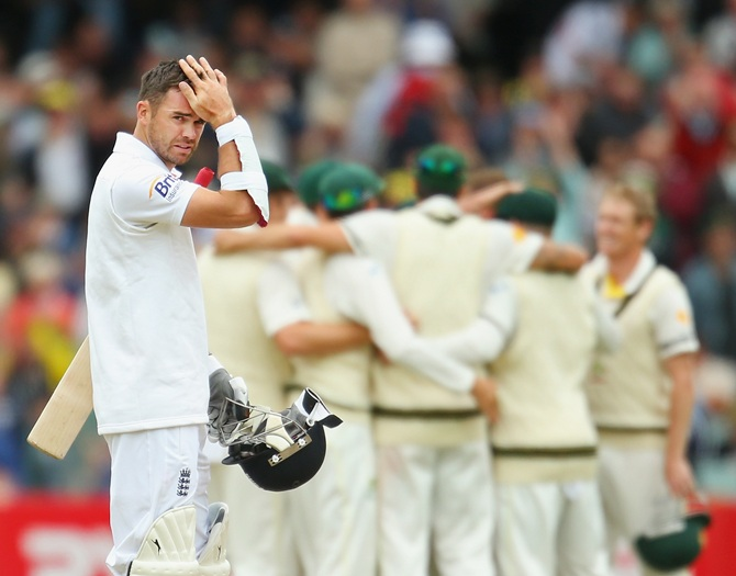 James Anderson of England looks on as Australia celebrate their victory