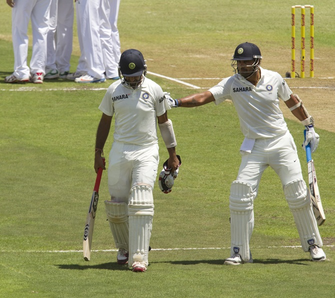 India's Cheteshwar Pujara is consoled by team mate Murali Vijay after getting out
