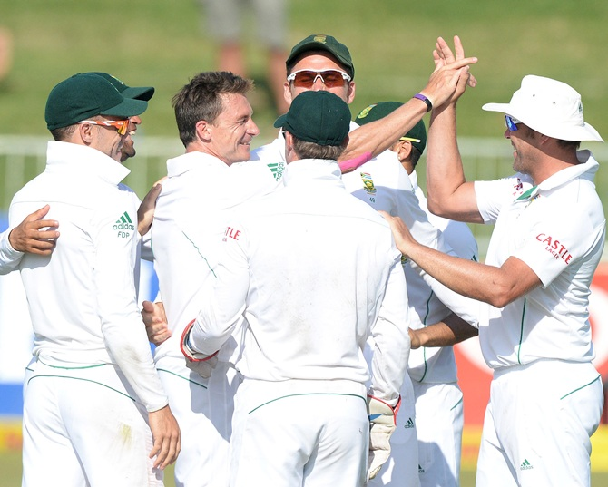 Dale Steyn (second left) and Jacques Kallis (right) of South Africa celebrate the wicket of MS Dhoni
