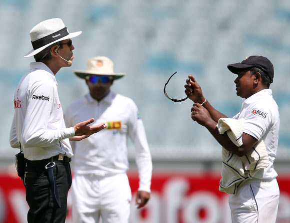 Umpire Nigel Llong speaks to Sri Lanka spinner Rangana Herath