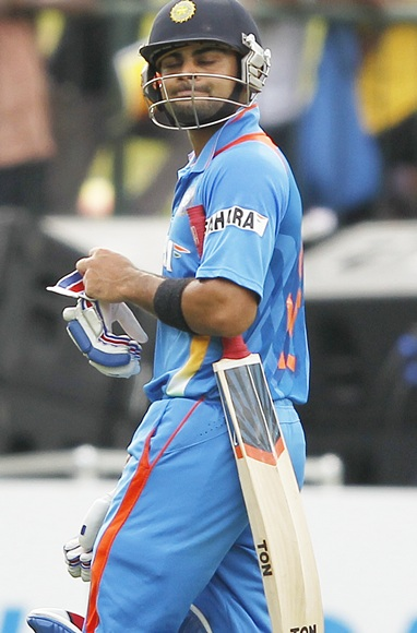 India's captain Virat Kohli reacts as he walks off the field after his dismissal