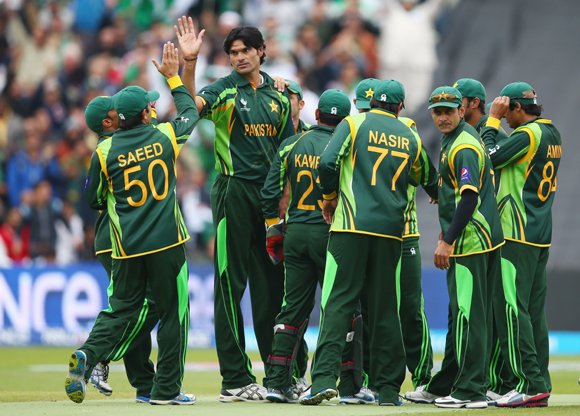 Muhammad Irfan (3L) of Pakistan receives team mates congratulations after taking the wicket of Faf Du Plessis of South Africa