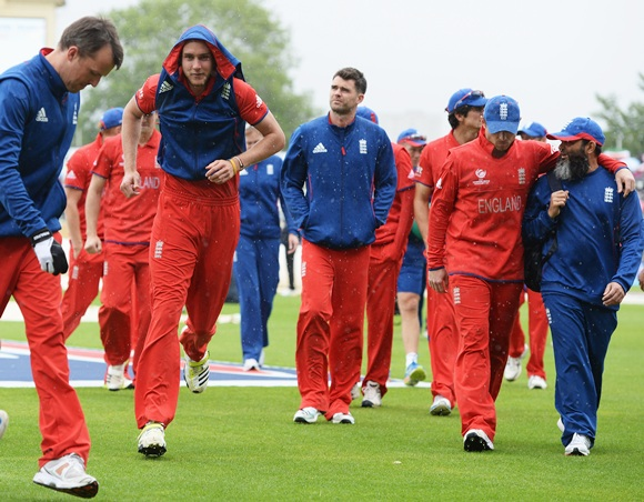 Stuart Broad of England jogs back to the dressing room with team mates after rain begins to fall prior to the ICC Champions Trophy final