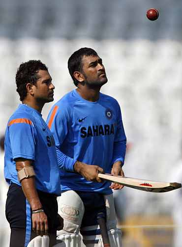 India's captain Mahendra Singh Dhoni (right) plays with a ball as teammate Sachin Tendulkar watches