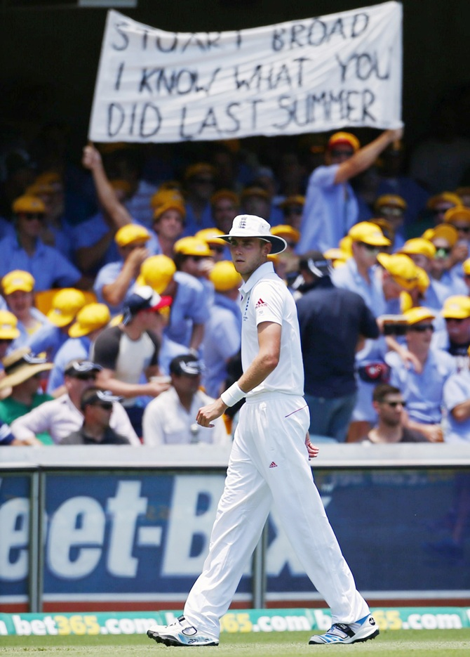 England's Stuart Broad stands in the outfield in front of a spectator's sign about him