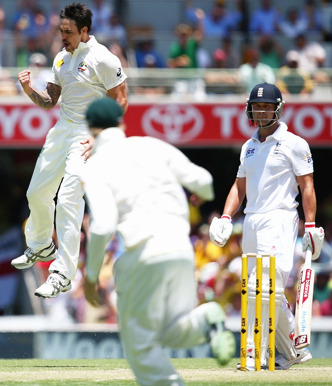 Mitchell Johnson of Australia celebrates after taking the wicket of Jonathan Trott of England