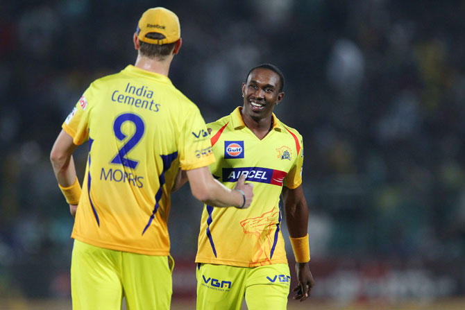 Chris Morris of Chennai Super Kings congratulates teammate Dwayne Bravo on the wicket of Stuart Binny