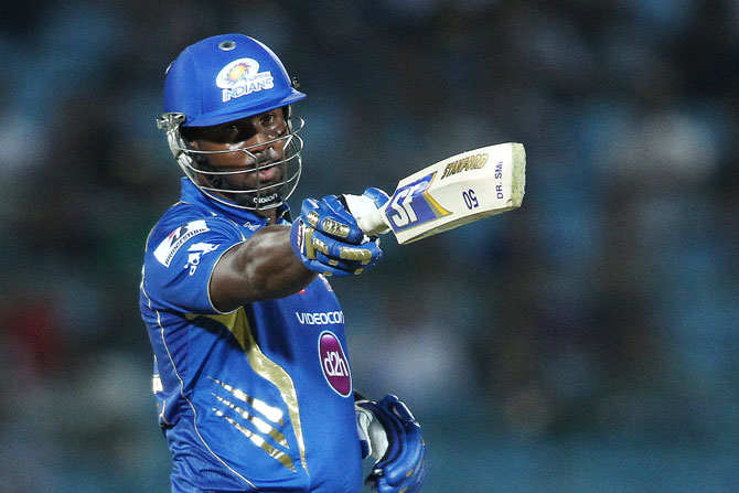 Dwayne Smith of Mumbai Indians raises his bat to the dug out after reaching his fifty