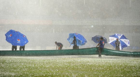 Groundstaff stuggle to cover the field as heavy rain and hailstones lash the ground