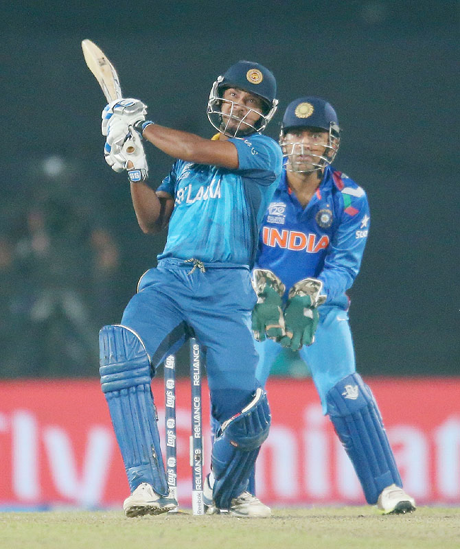 Kumar Sangakkara of Sri Lanka bats as MS Dhoni of India looks on