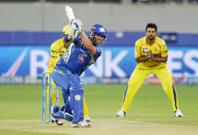 Corey Anderson hits a shot as Suresh Raina looks on