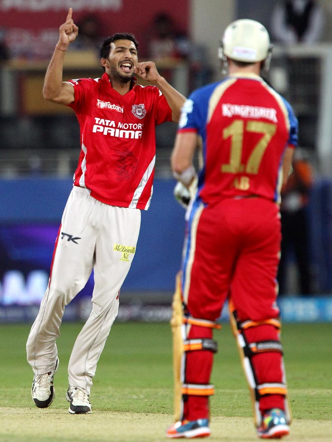 Rishi Dhawan celebrates as AB de Villiers walks back after his dismissal