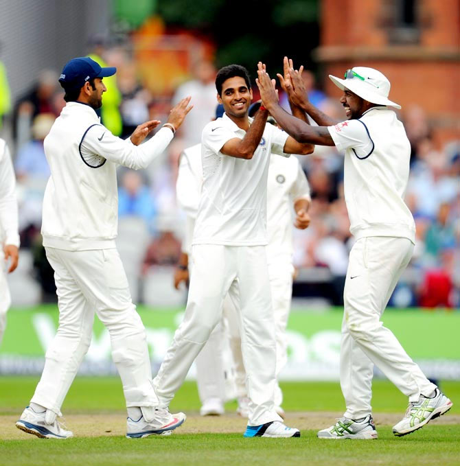 Bhuvneshwar Kumar (centre) is congratulated by team mates after he claimed the wicket of England batsman Chris Jordan