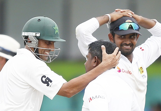 Pakistan's Younis Khan, left, talks with Sri Lanka's Rangana Herath, centre, who took his wicket as Lahiru Thirimanne looks on