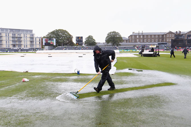Groundstaff sweep away puddles from the outfield in vain as play is abandoned in the first ODI