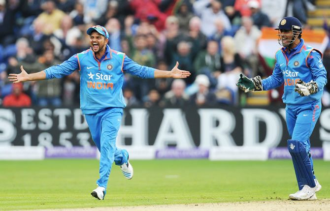 India fielders MS Dhoni (r) and Suresh Raina celebrate after India had dismissed Jos Buttler