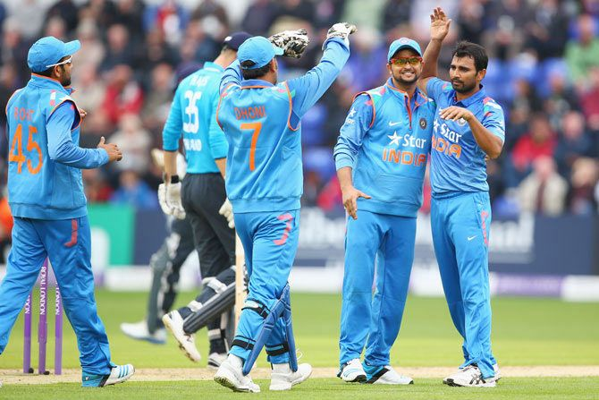 Mohammed Shami,right, of India celebrates with Suresh Raina, second right, and MS Dhoni after capturing the wicket of Alastair Cook of England