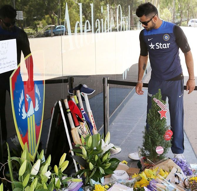 Virat Kohli of India leaves a bat and cap at a memorial for Phil Hughes outside the Adelaide Oval