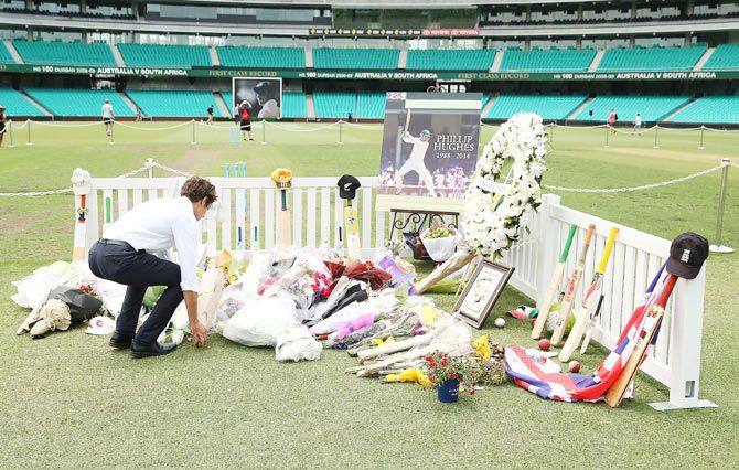 People lay flowers at the Randwick End of the SCG prior to the gathering of people to watch the funeral service of Phillip Hughes